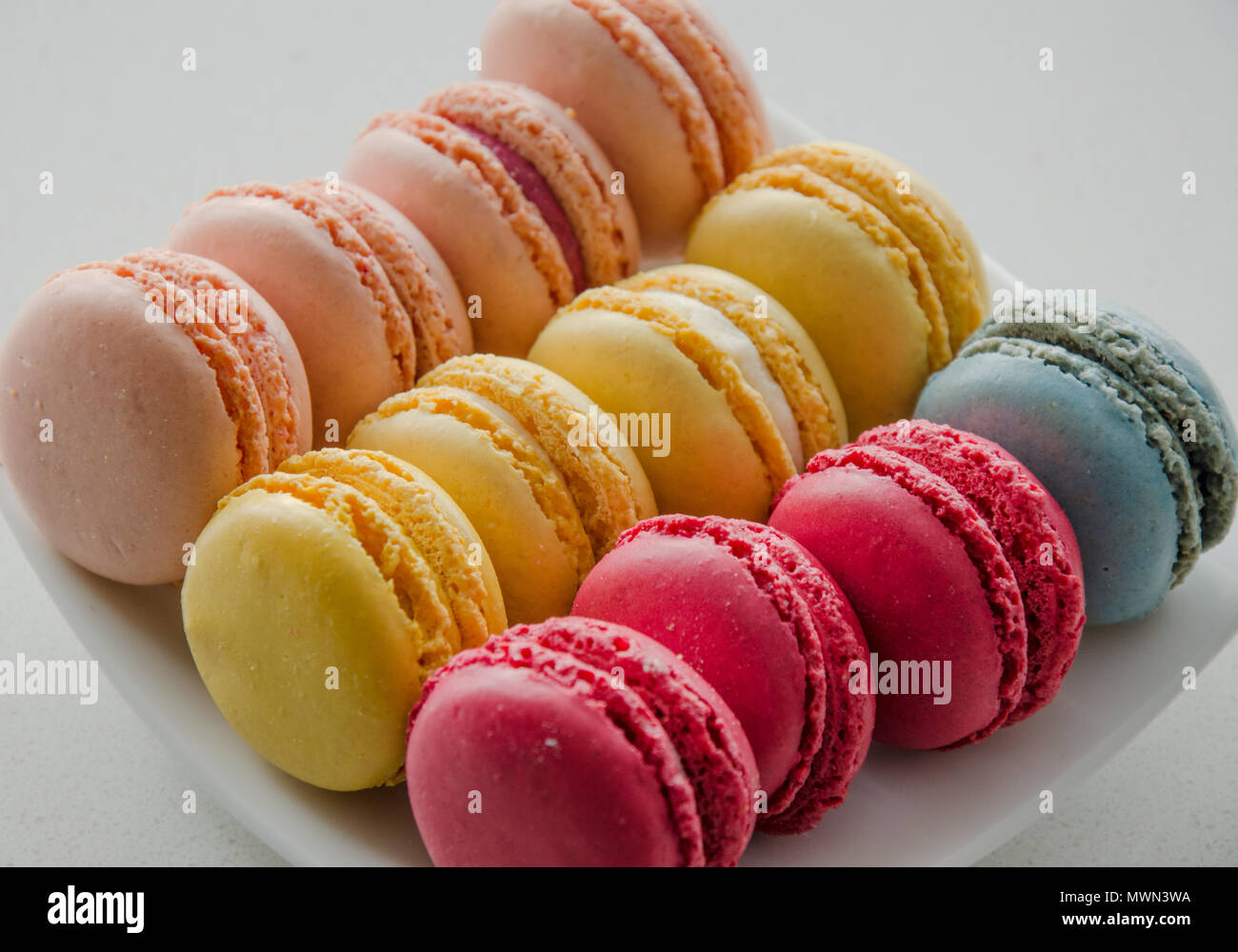 Delicious Colourful French Macarons on a plate as delicate savory dessert - Stock Image