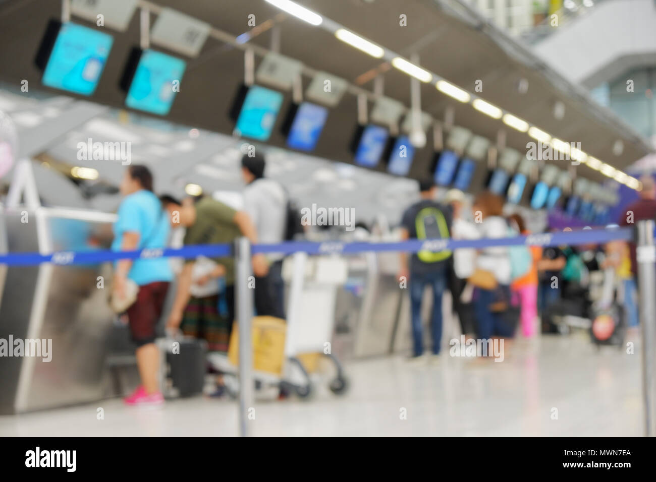 Blurred defocused image of passengers check in at the check-in counter at the international airport. Royalty high-quality stock image of people waitin - Stock Image