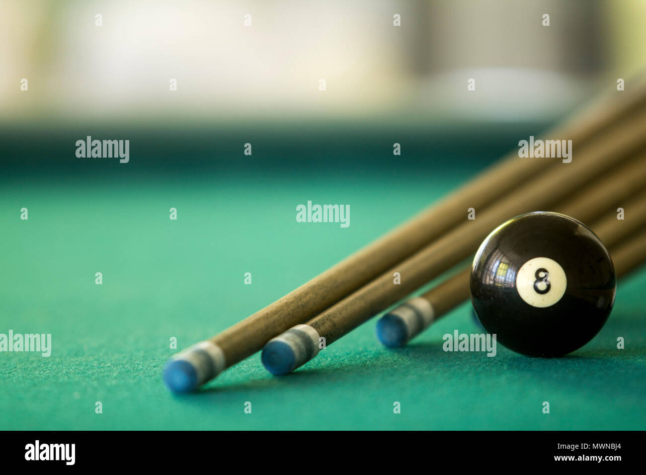 Close Up of a eight black billiard ball on a green table - Stock Image