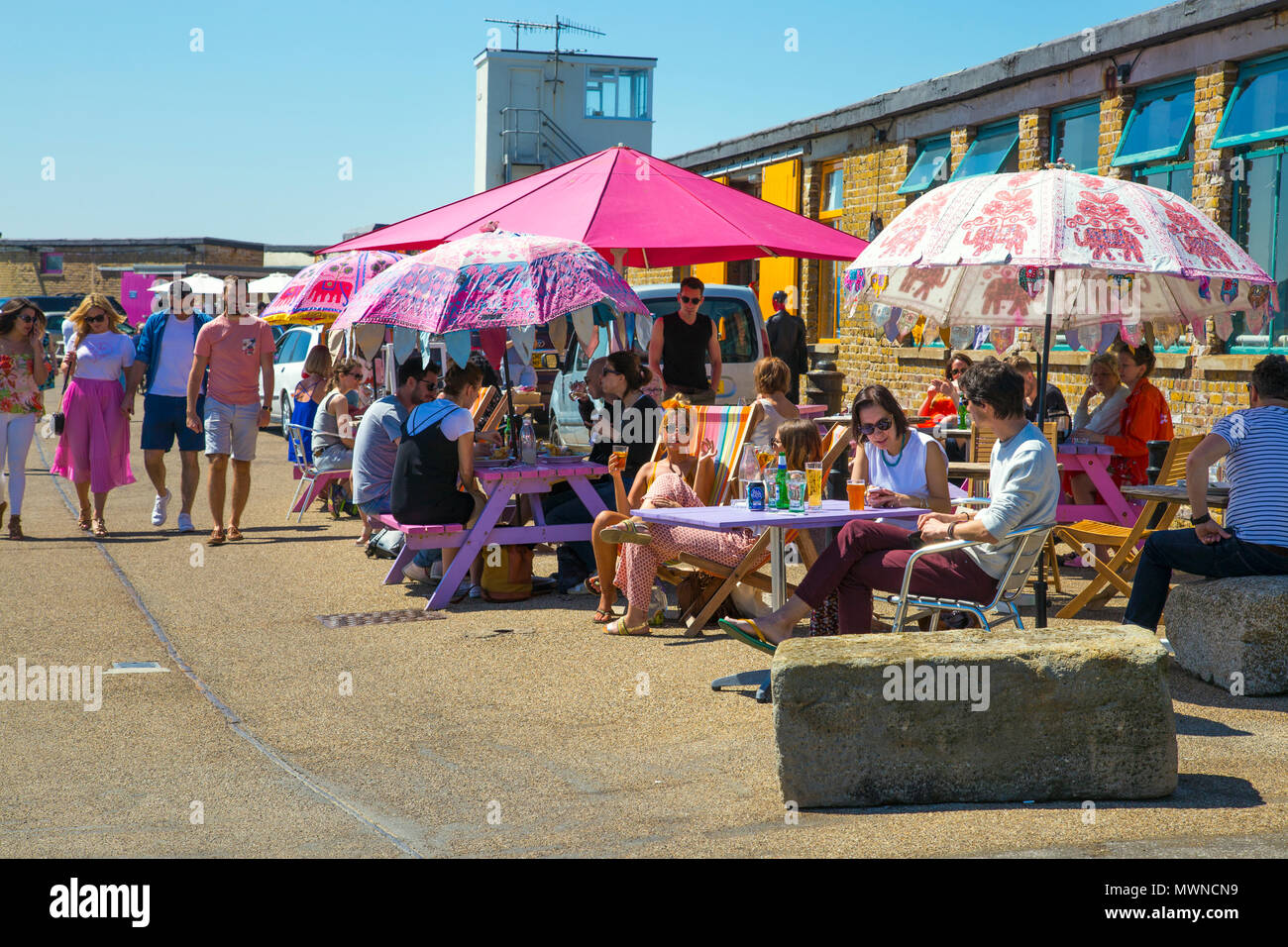People sitting at cafe (BeBeached Cafe) tables on a hot summer day at the Harbour Arm in Margate, UK - Stock Image