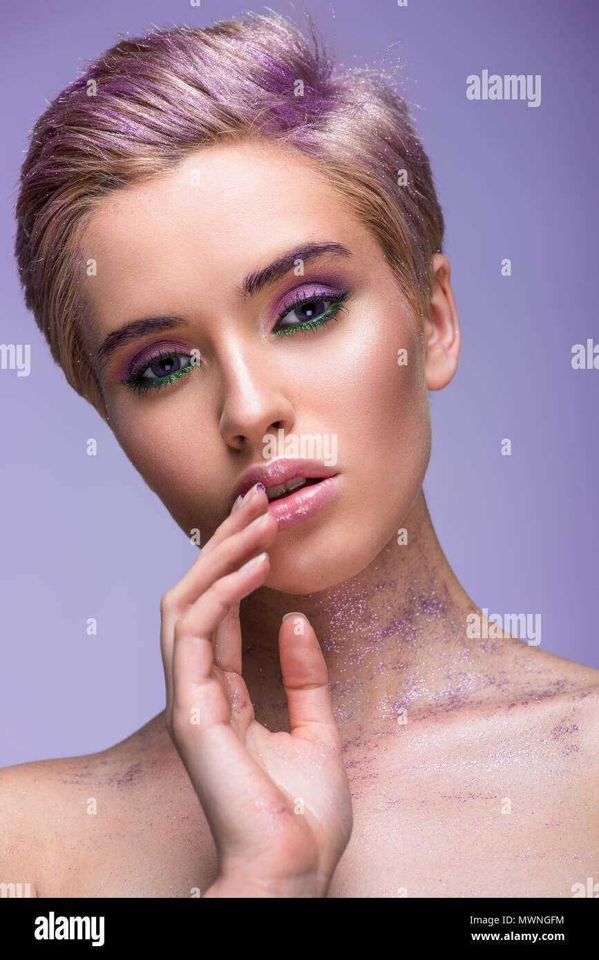 bc34c2cd649 attractive woman with violet glitter on neck and short hair touching lips  isolated on violet -