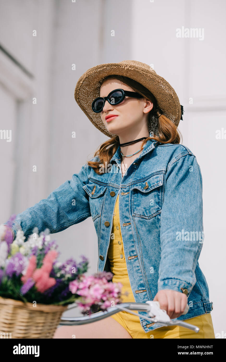 attractive girl in hat, sunglasses and denim jacket riding bicycle on street Stock Photo