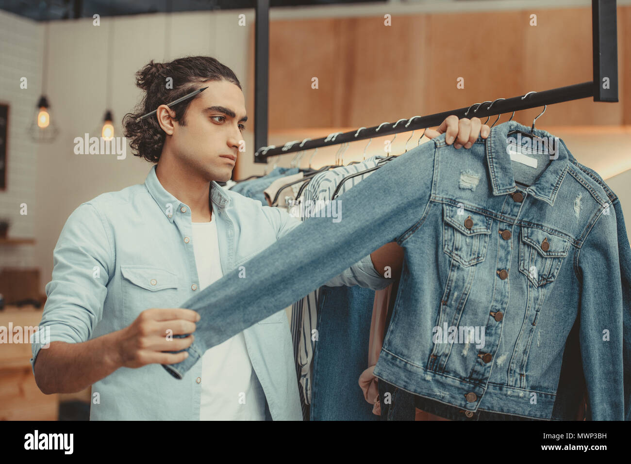 serious young shop owner holding denim jacket in boutique - Stock Image