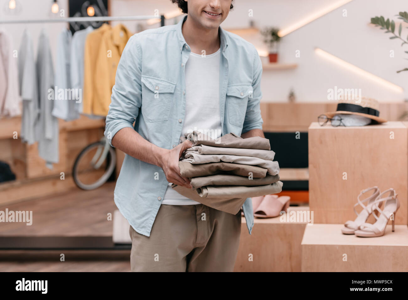cropped shot of young business owner holding pile of pants while working in boutique - Stock Image