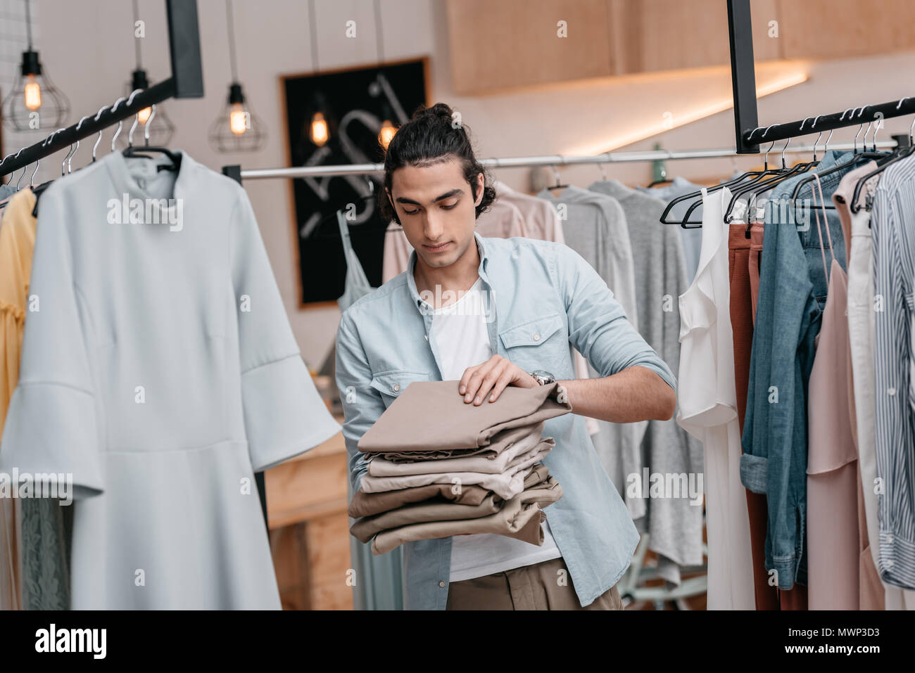young business owner holding pile of pants while working in boutique before opening - Stock Image