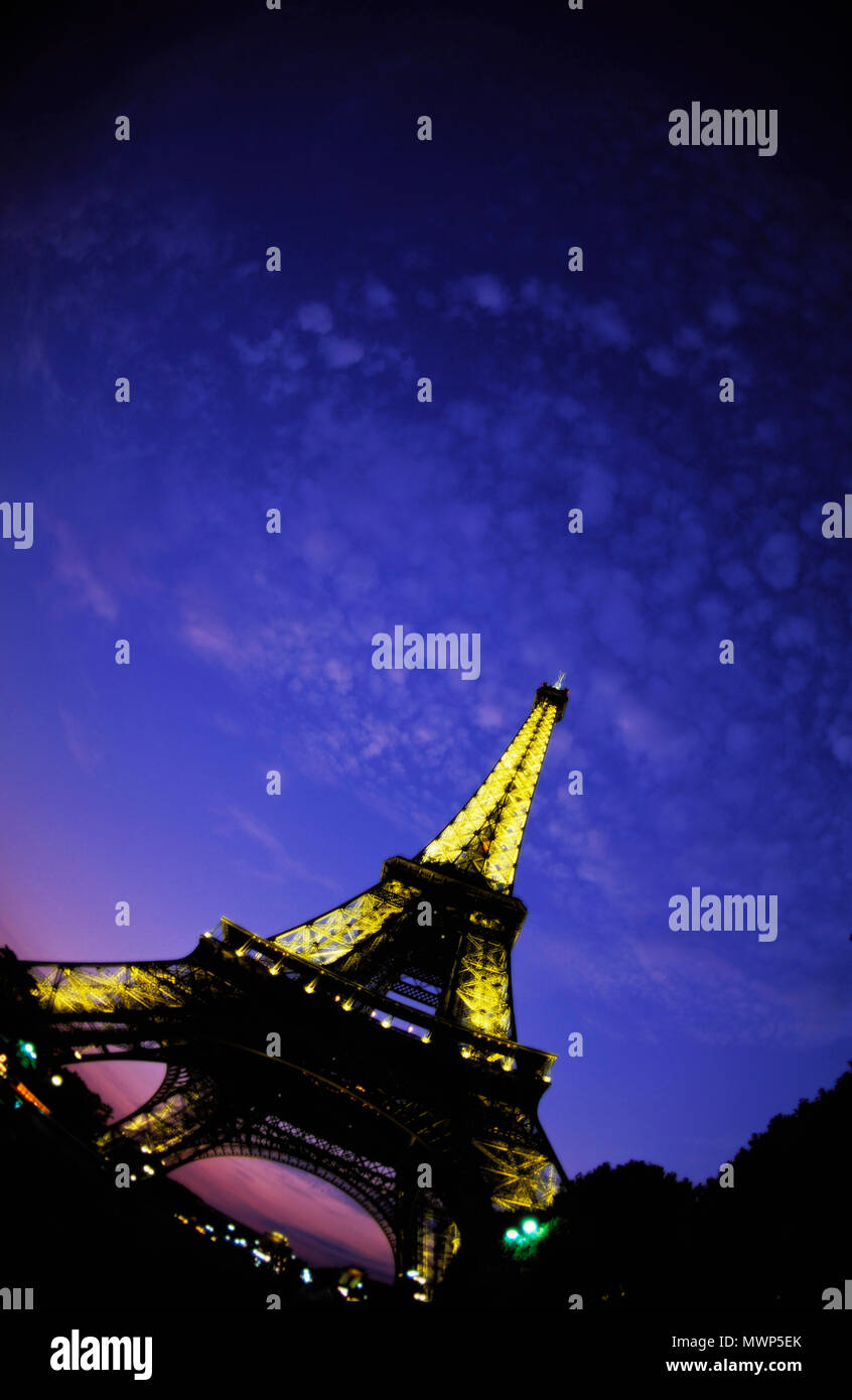 Eiffel Tower, looking northwest down Champ de Mars and up at dusk, depicting lights on a with little fluffy clouds and twilight glow, Paris, France - Stock Image