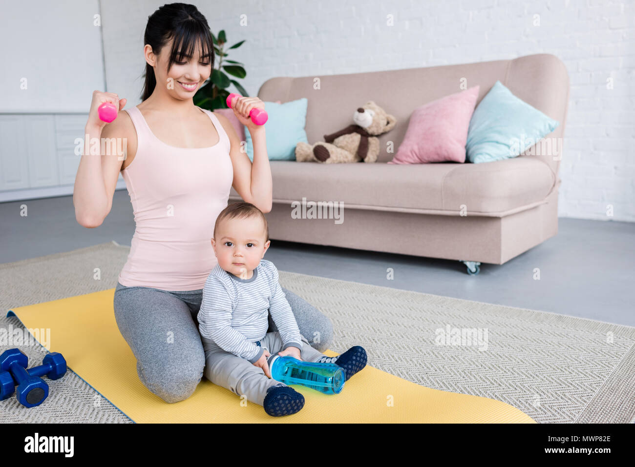 young smiling mother working out on yoga mat with her little child at home Stock Photo