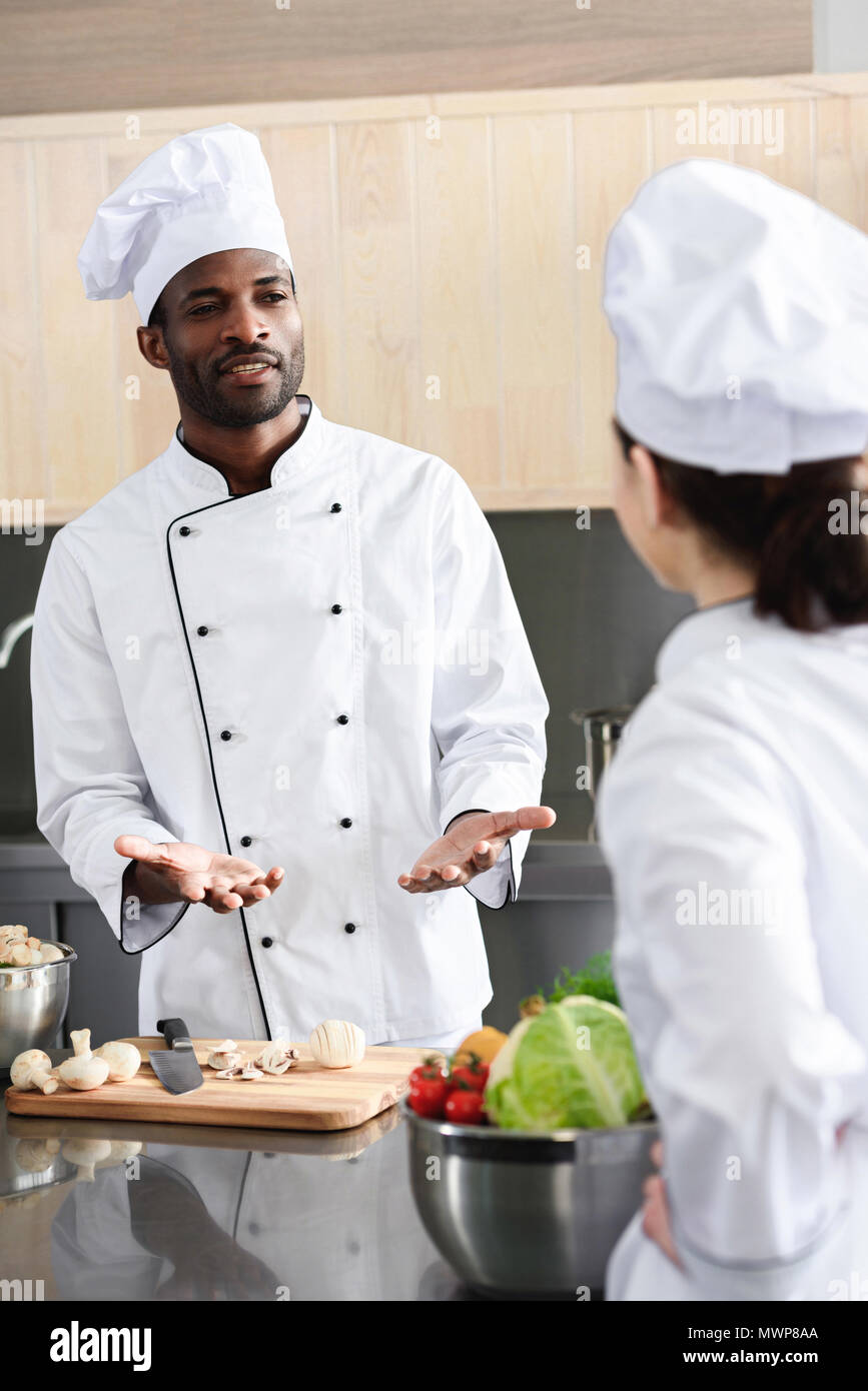 Multiracial chefs team discussing recipe and cooking on kitchen - Stock Image