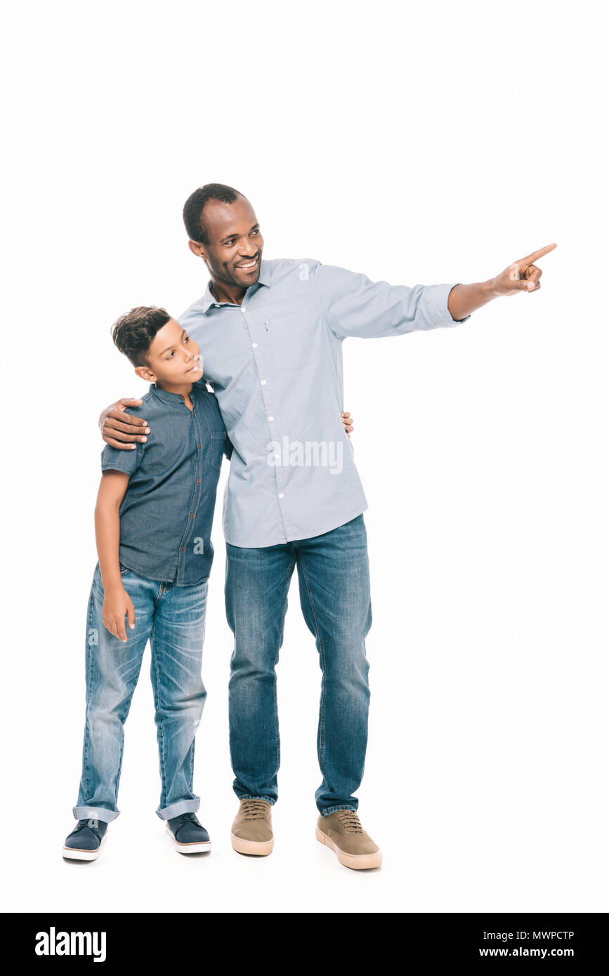 b25f831b1 smiling african american father and son standing together and pointing away  with finger isolated on white