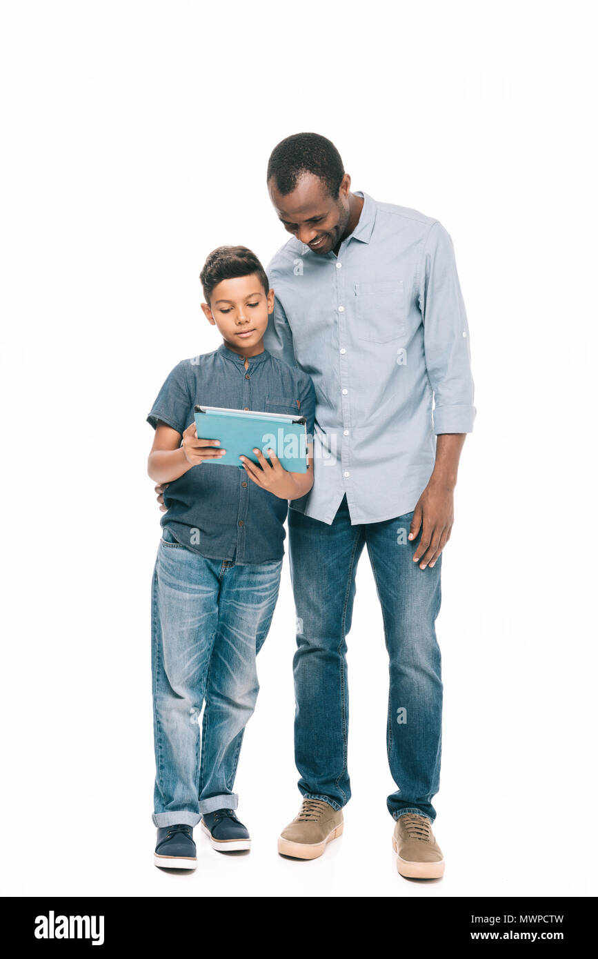60ed36ffd happy african american father and son using digital tablet while standing  together isolated on white