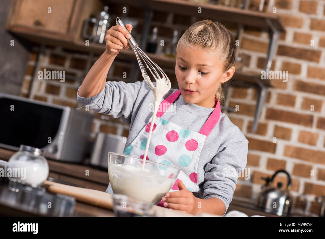portrait of preteen girl in apron with whisk cooking alone at home - Stock Image