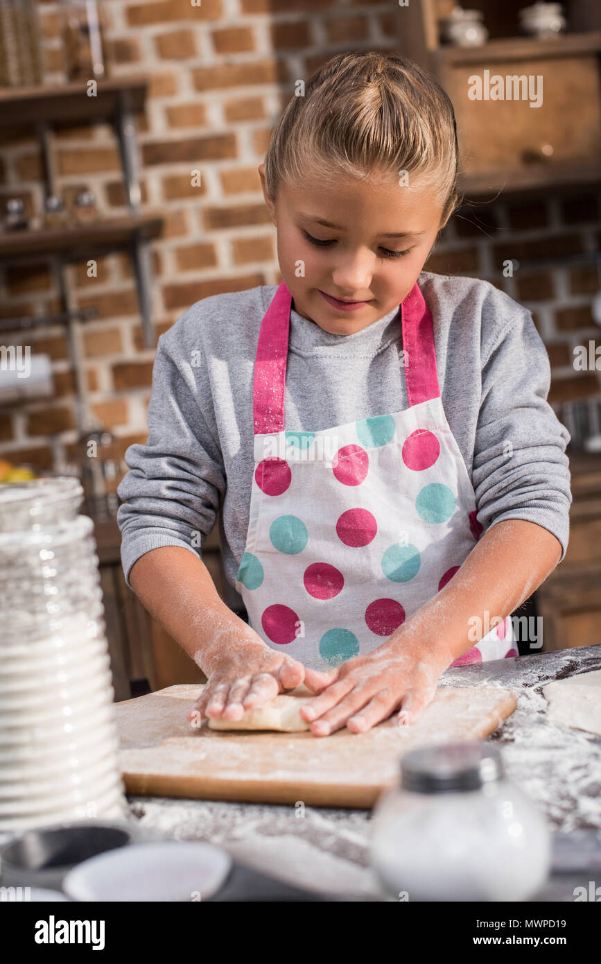 portrait of focused little girl rolling raw dough while cooking at home - Stock Image