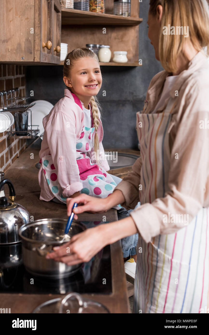 side view of smiling preteen girl sitting on counter and watching mother cooking at home - Stock Image