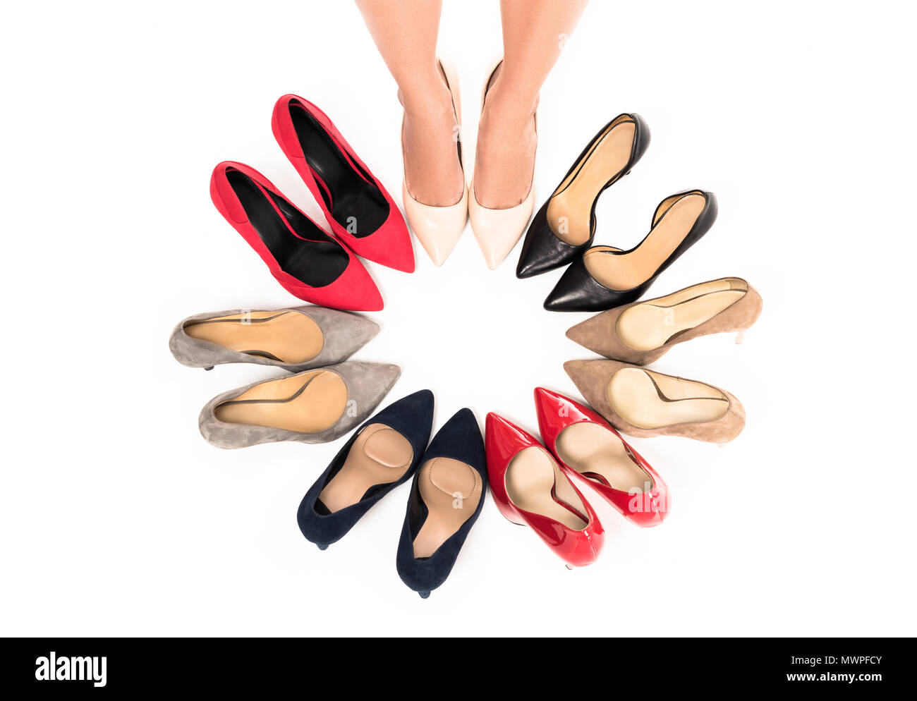 partial view of woman standing in circle with arranged stylish high heels isolated on white - Stock Image