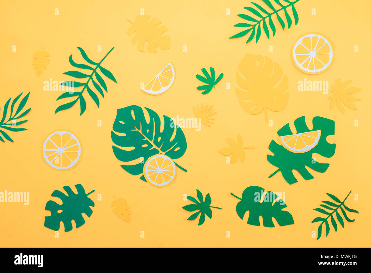 Tropical leaves pattern. Green monstera and fern leaves with orange and lemon slices on a bright yellow background. Summer vacation concept with paper craft fruits - Stock Image