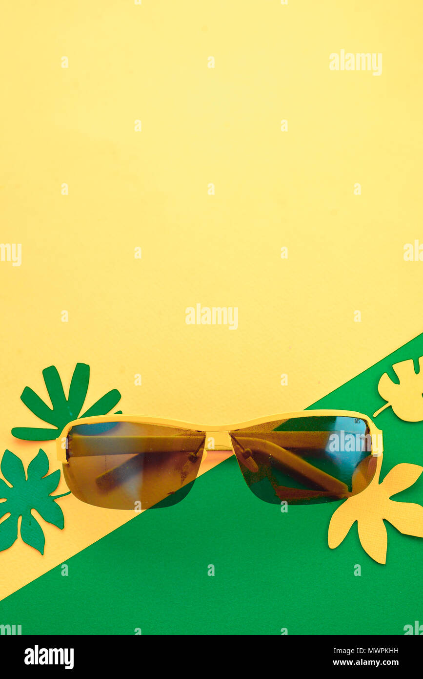 Sunglasses on a bright yellow background with green and yellow tropical leaves. Sunny summer flat lay with copy space. - Stock Image