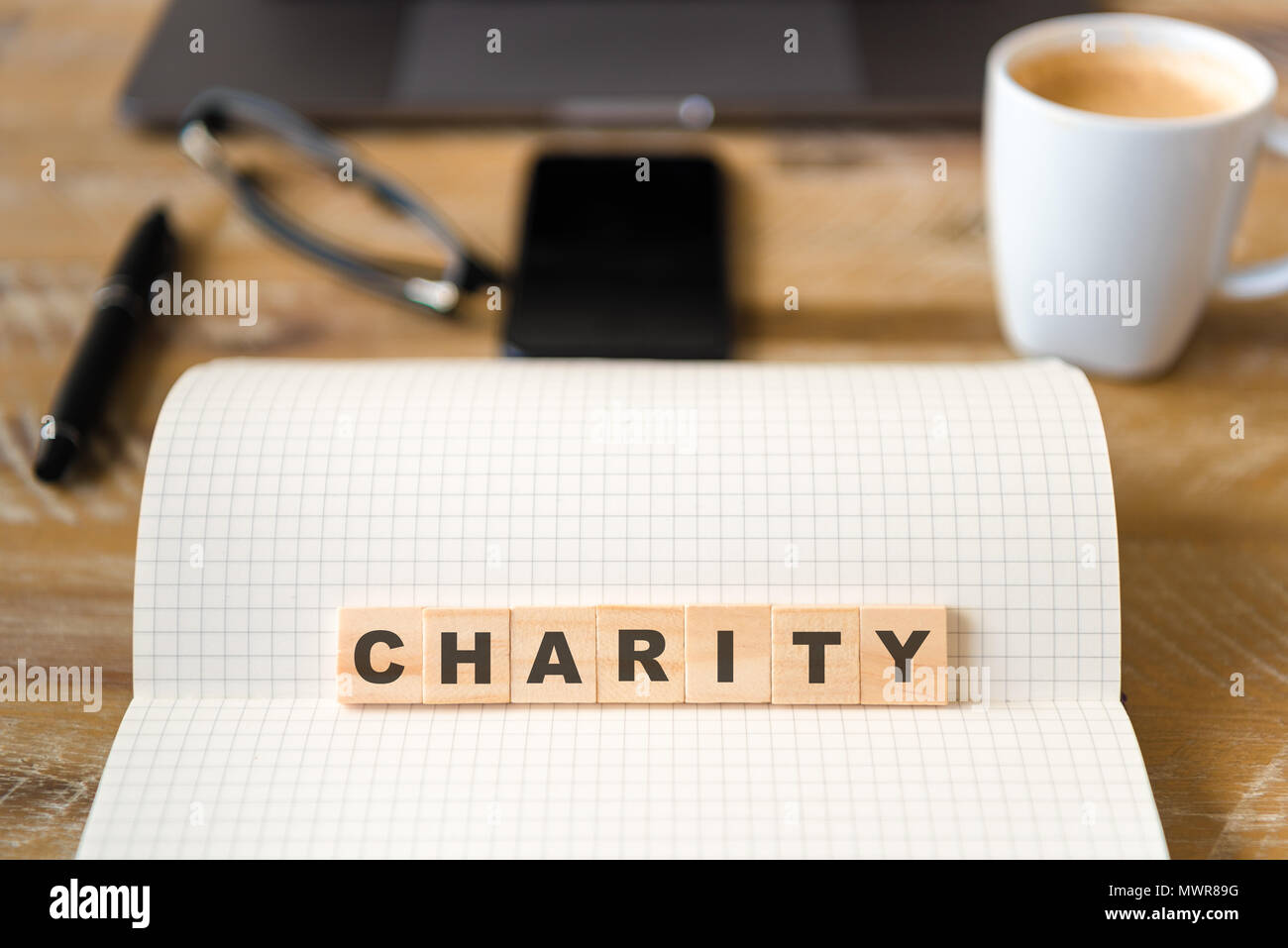 Closeup on notebook over wood table background, focus on wooden blocks with letters making Charity text. Stock Photo