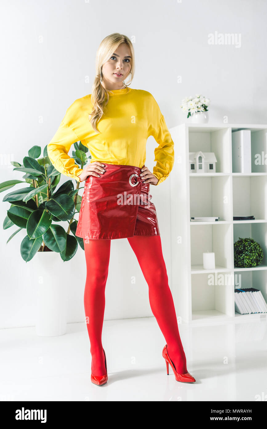 fashionable businesswoman in red skirt posing in modern office - Stock Image