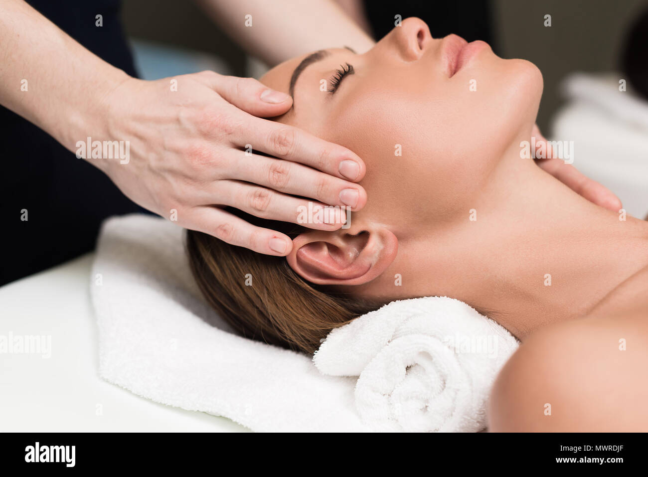 young woman relaxing and having head massage in spa salon - Stock Image