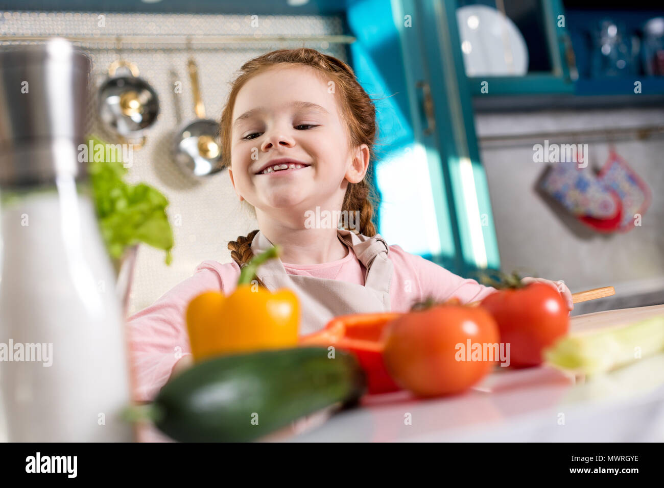 adorable little child smiling while cooking in kitchen - Stock Image