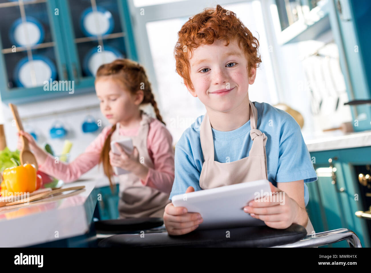 cute little boy with digital tablet smiling at camera while child with smartphone cooking behind - Stock Image
