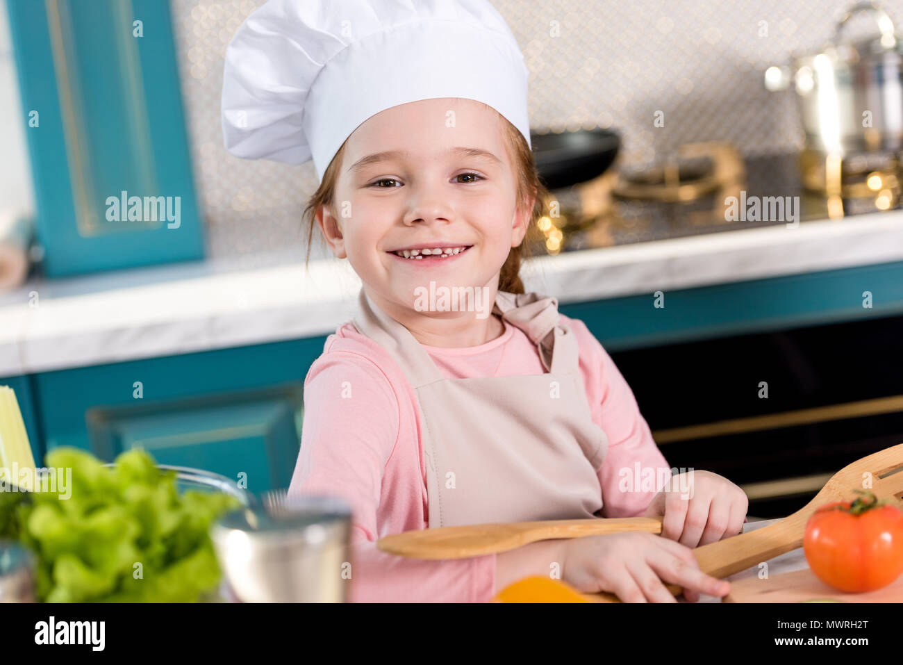 adorable child in chef hat and apron smiling at camera while cooking in kitchen - Stock Image