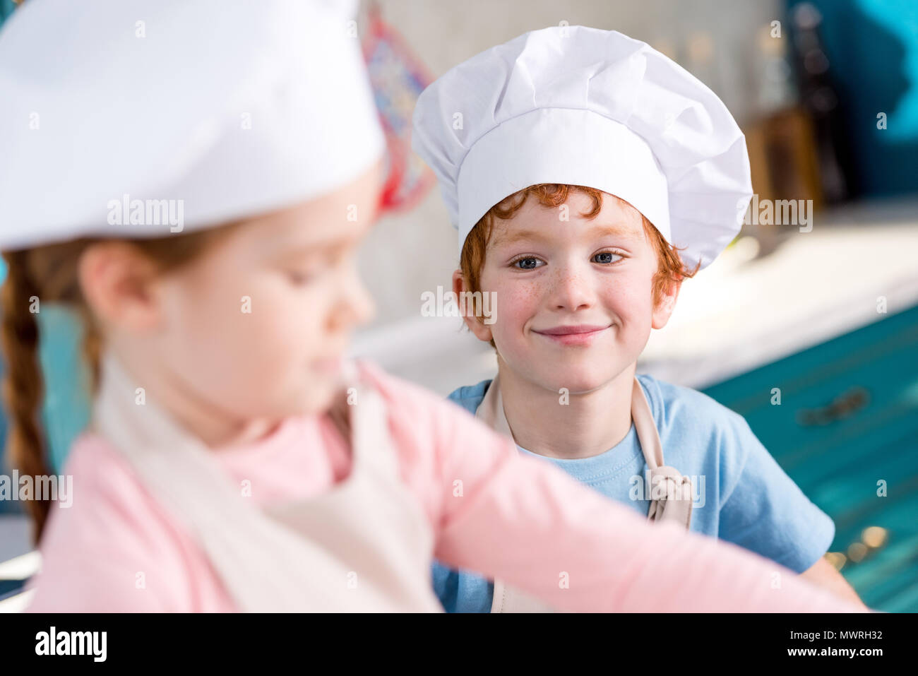 adorable smiling little boy in chef hat looking at friend cooking on foreground - Stock Image