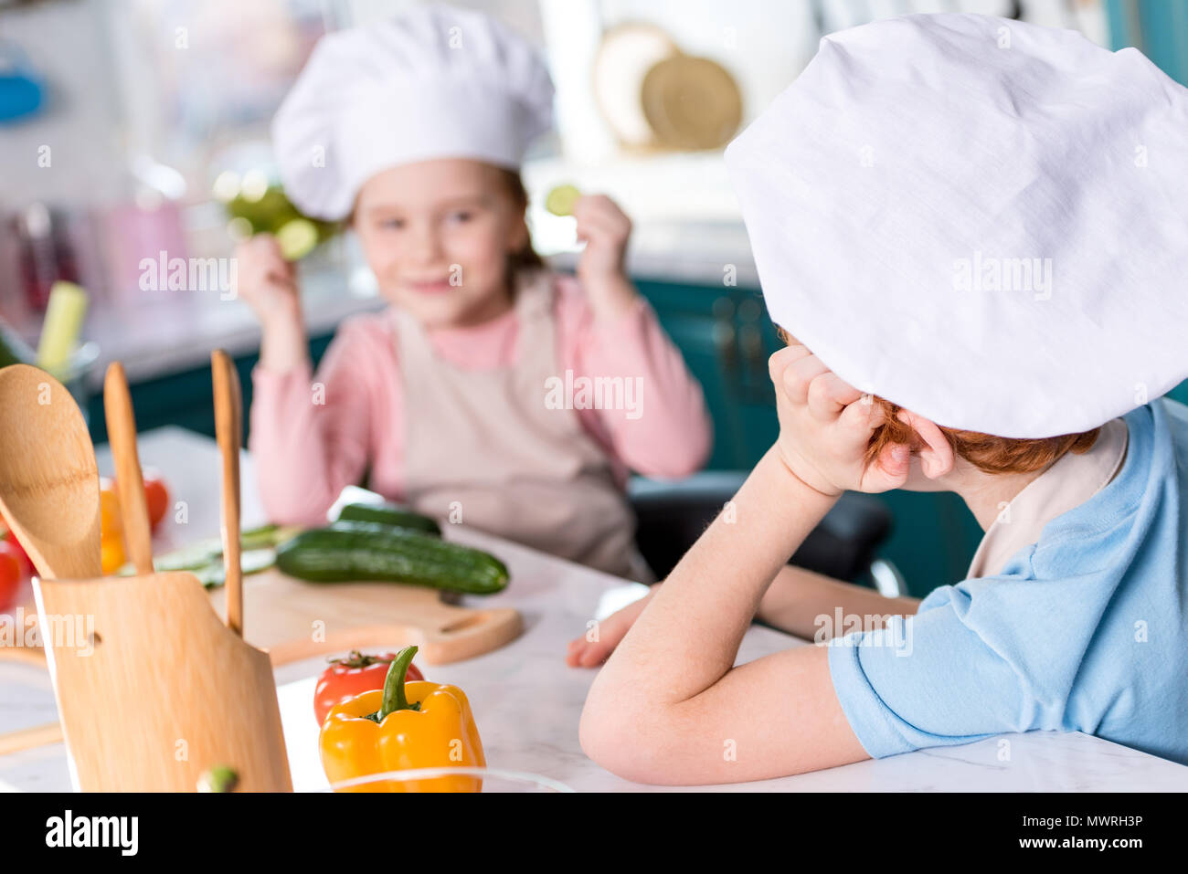 adorable children in chef hats looking at each other while cooking together in kitchen - Stock Image