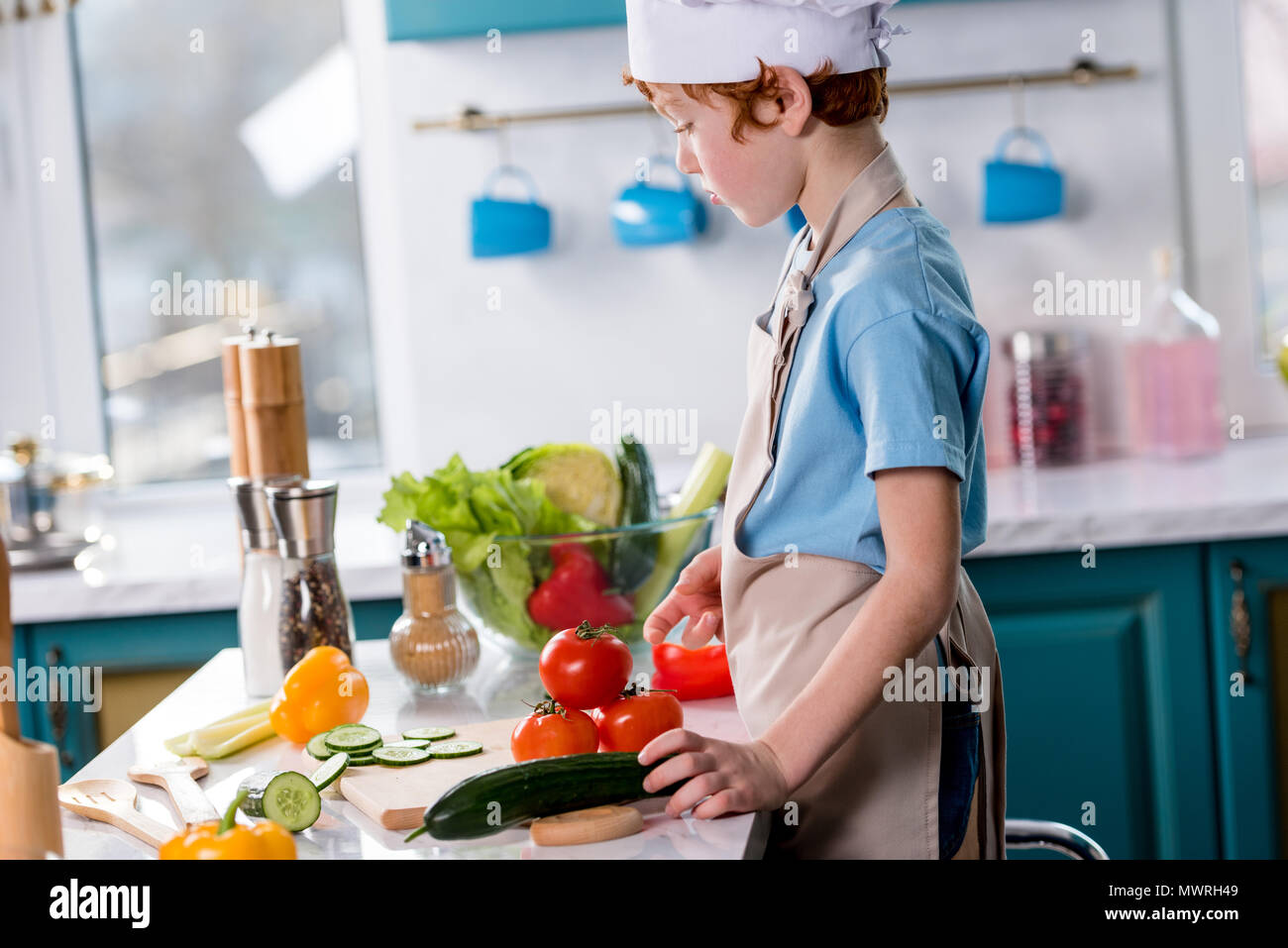 side view of cute little boy in chef hat and apron cooking in kitchen - Stock Image