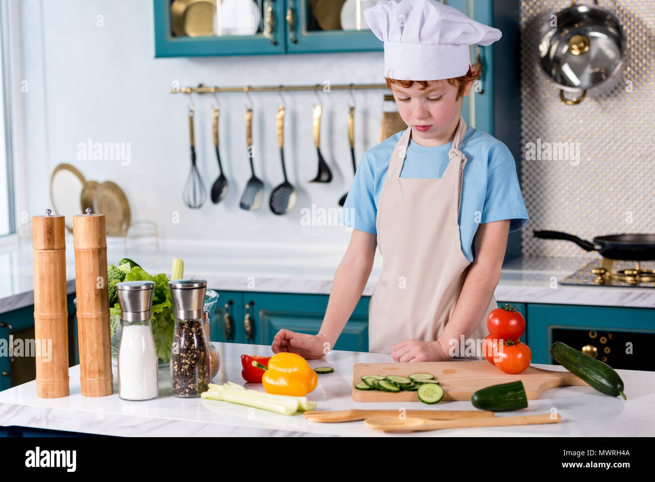 cute little boy in chef hat and apron cooking in kitchen - Stock Image