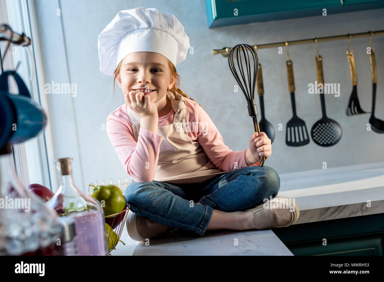 cute child in chef hat holding whisk and smiling at camera in kitchen Stock Photo