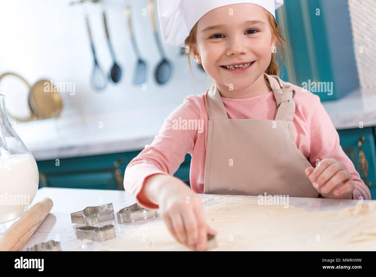 adorable child in chef hat and apron smiling at camera while preparing cookies - Stock Image