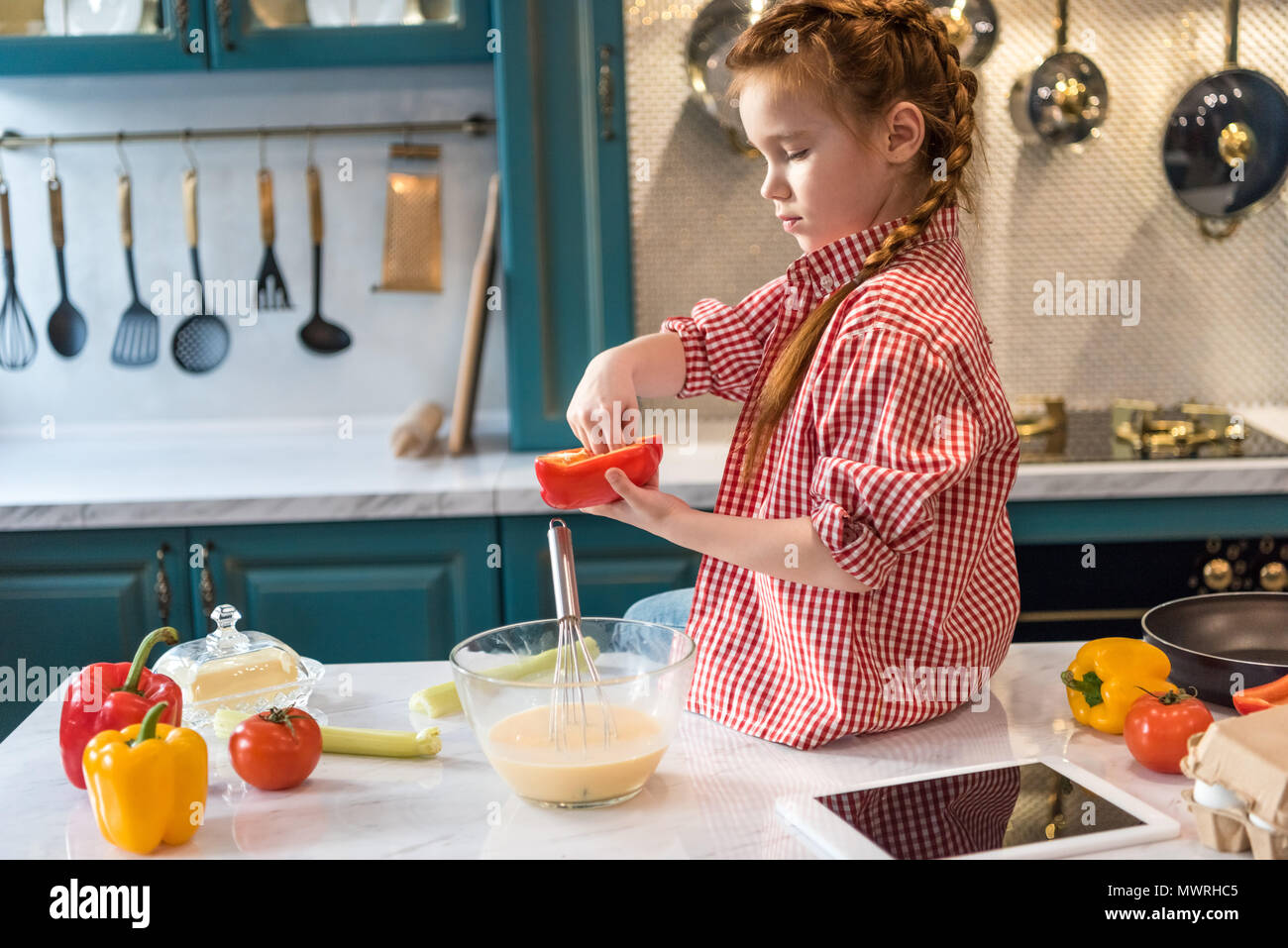 adorable little child cooking while sitting on kitchen table - Stock Image