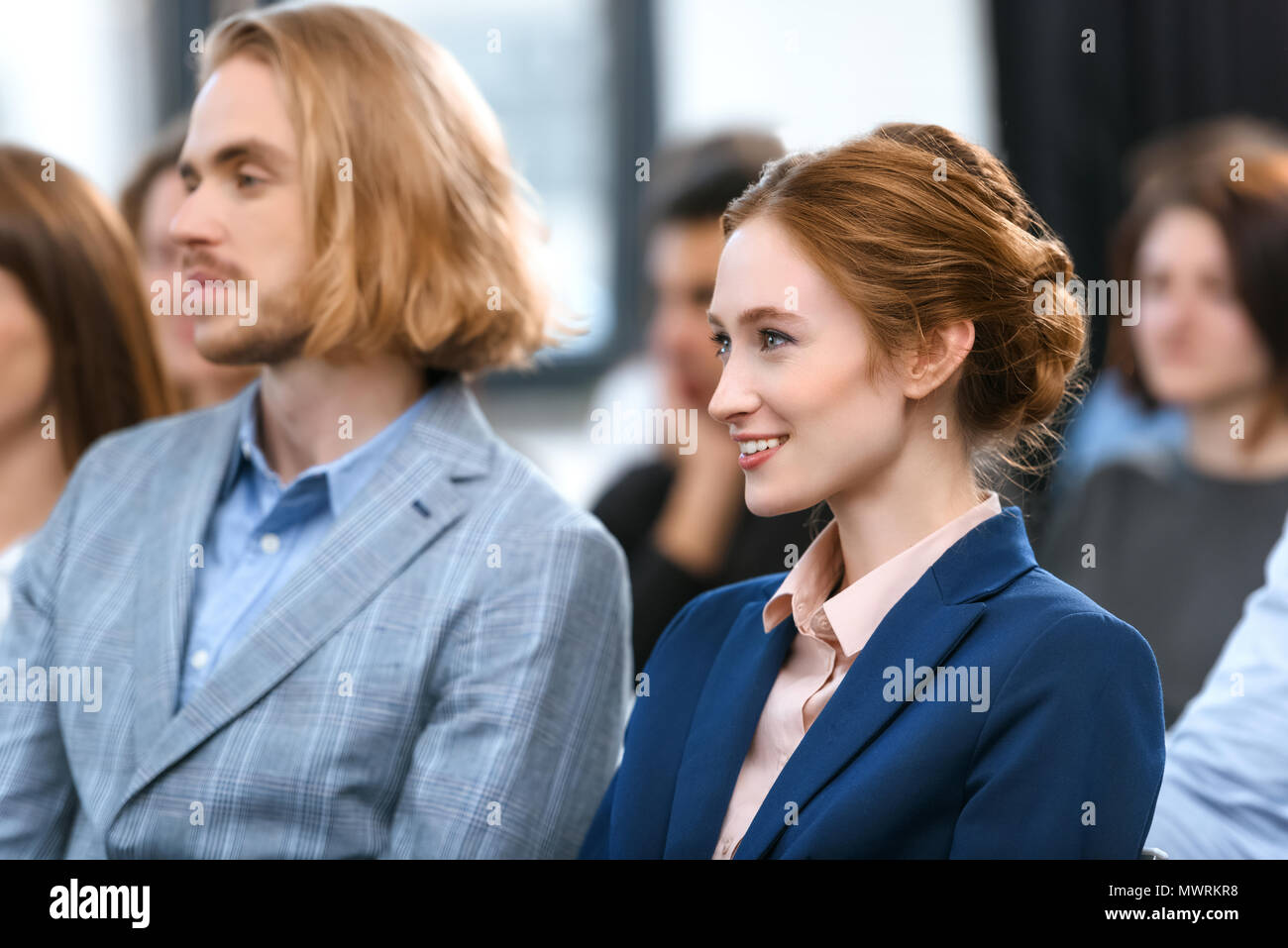 man and woman in formal suits sitting near each other at meeting - Stock Image
