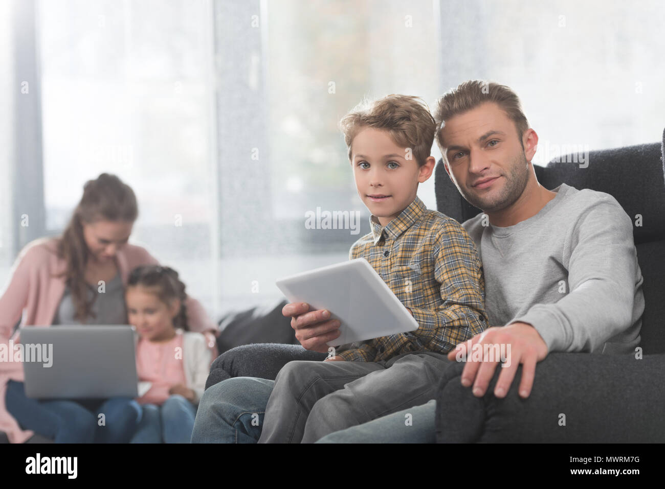 Young Boy Sitting In Lap Of His Dad While He Is Holding A Digital