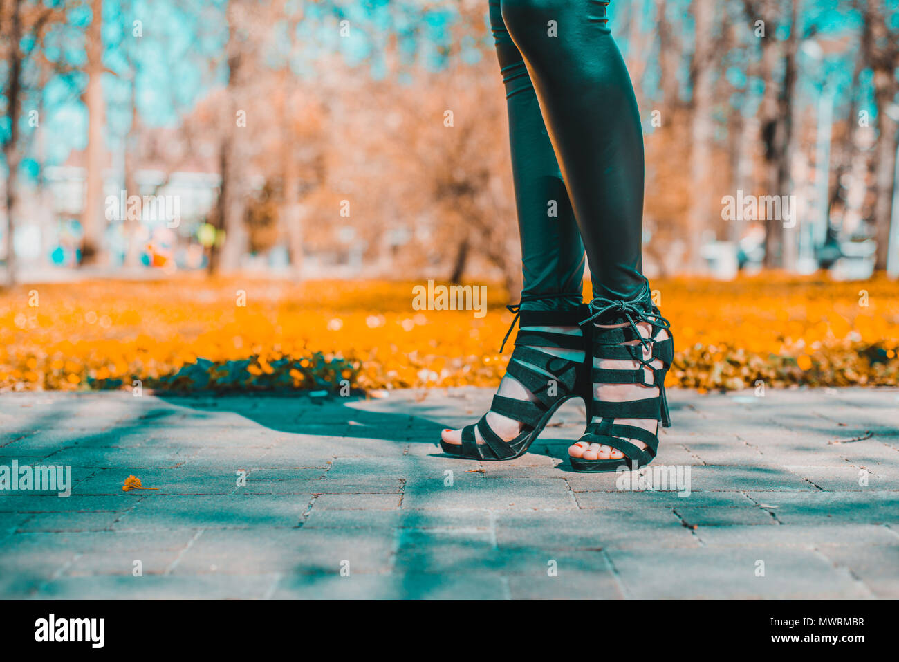 Legs view of a woman walking.The girl in black pants moves around park outside. Beuty and fashion concept. - Stock Image