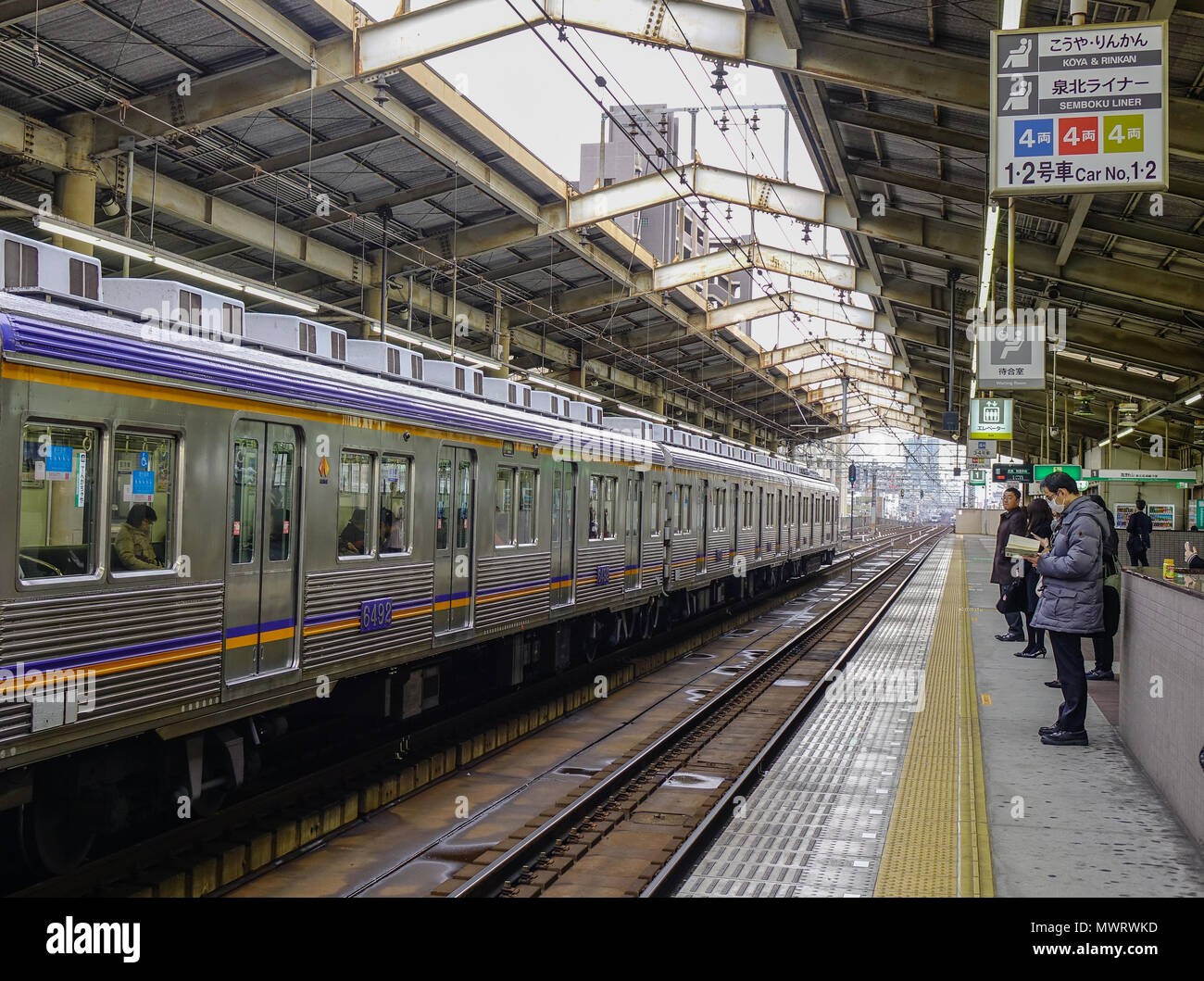 Osaka, Japan - Nov 24, 2016. A train stopping at a JR Railway Station. The railway system in Japan has a high reputation for punctuality and safety. - Stock Image