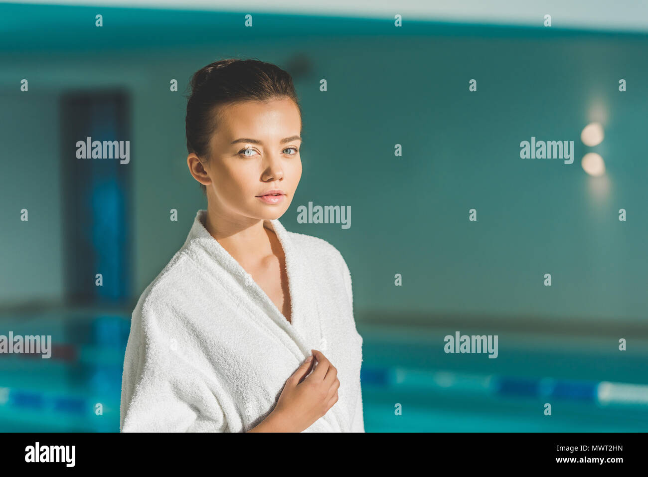beautiful young woman in bathrobe in front of swimming pool at spa - Stock Image