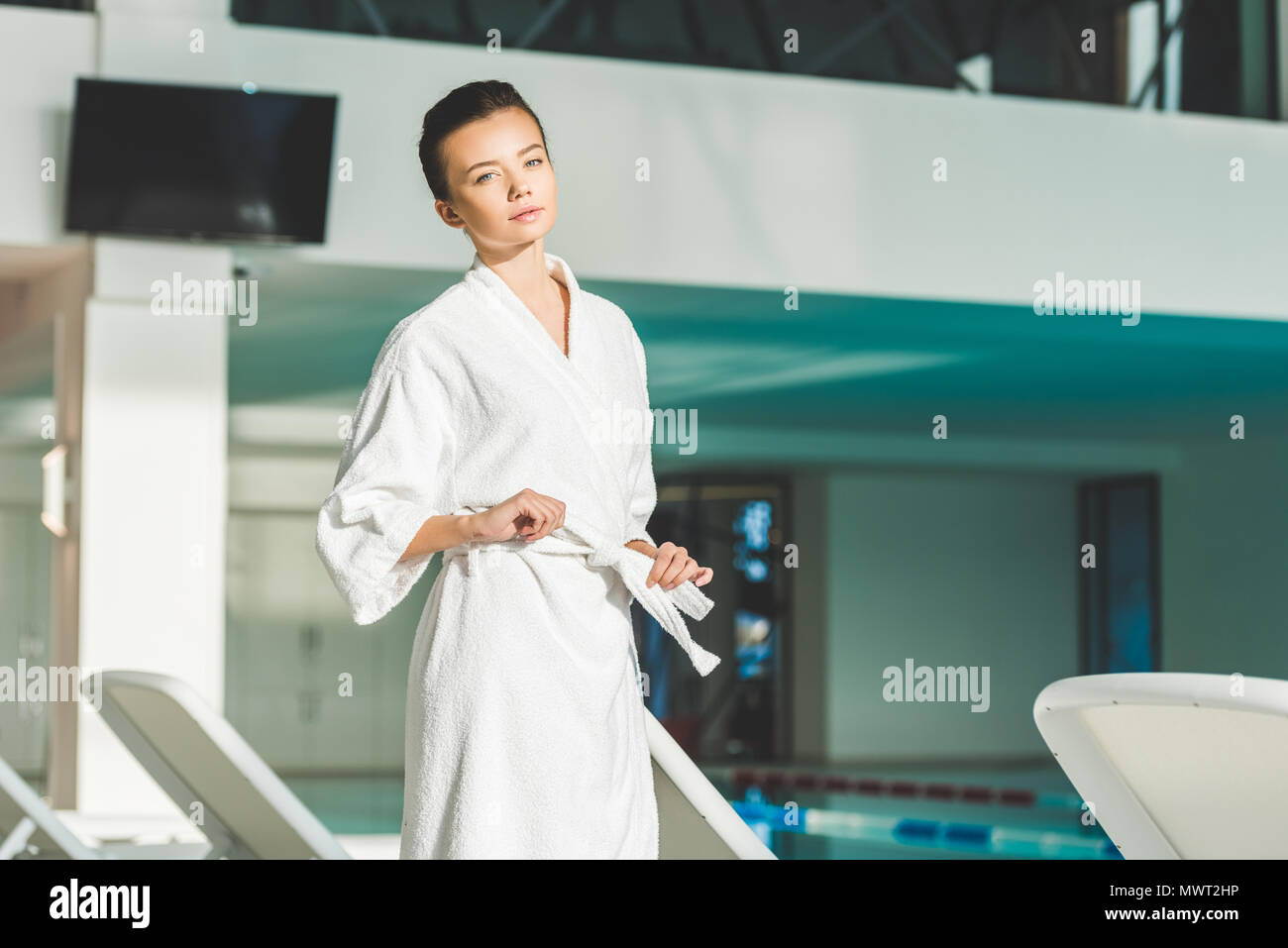 beautiful young woman tying up belt of bathrobe at spa - Stock Image