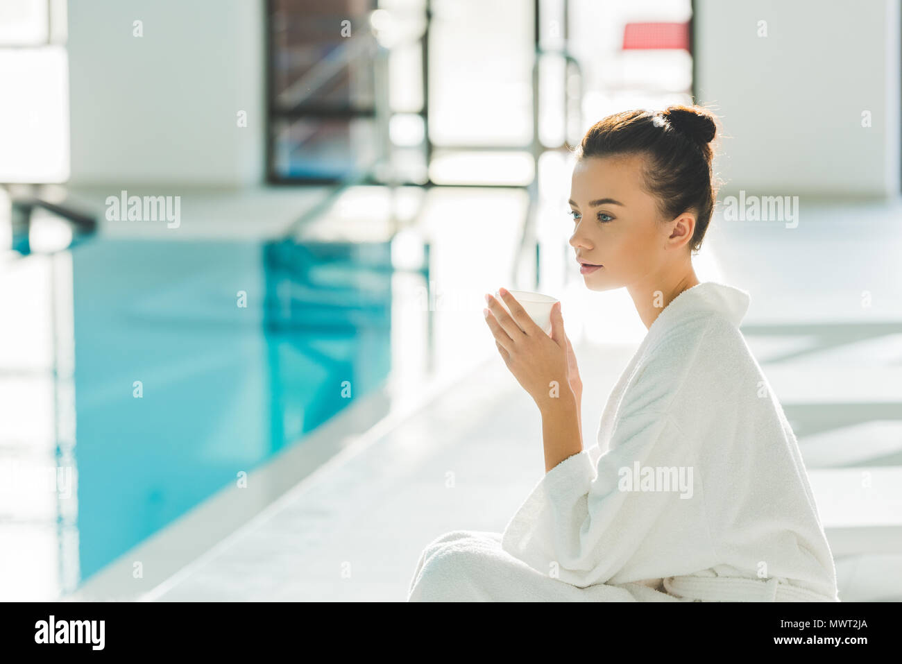thoughtful young woman in bathrobe with cup of coffee at spa - Stock Image