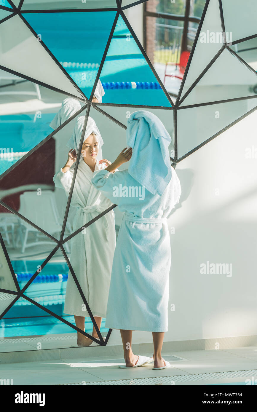 young woman in bathrobe and towel looking at mirror in spa center - Stock Image