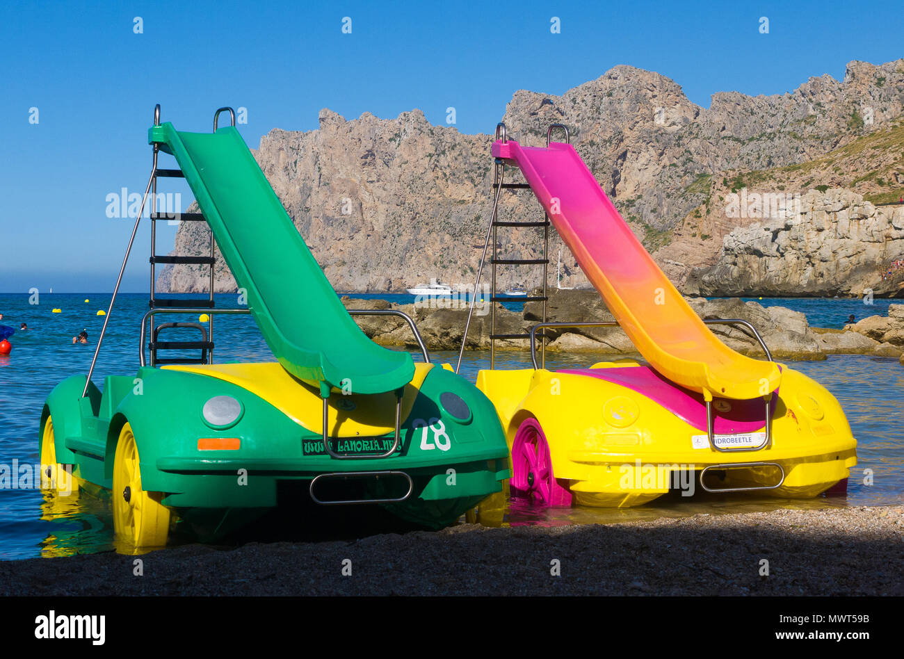 Two brightly coloured pedalos parked on a beach in Cala San Vicente in Mallorca, Spain. Stock Photo