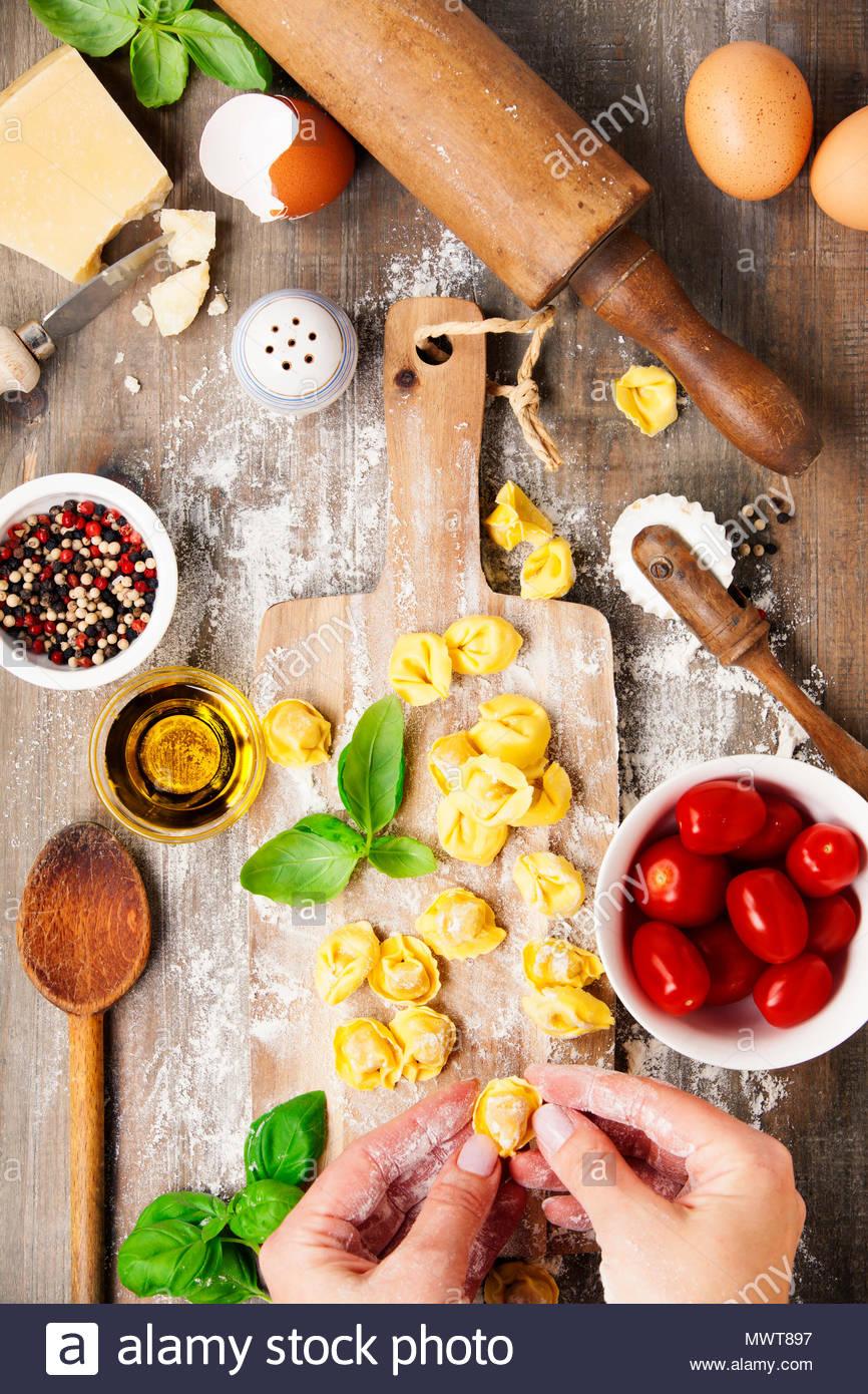 raw italian pasta tortellini on wooden board - Stock Image