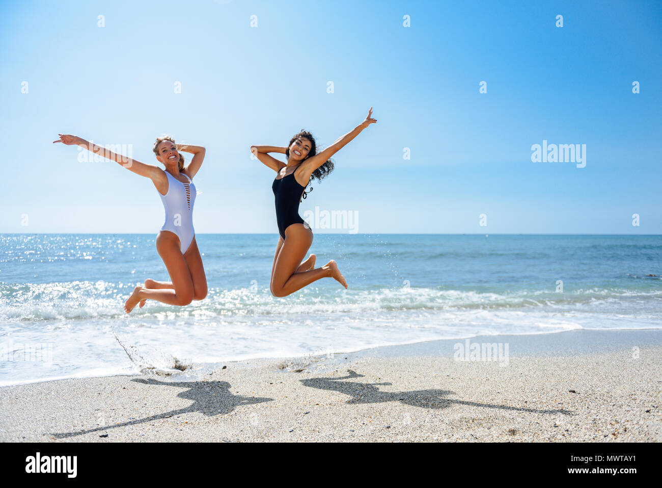 ef01f6d3250d5 Two funny girls with beautiful bodies in swimwear jumping on a tropical  beach. Funny caucasian and arabic females wearing black and white swimsuits.