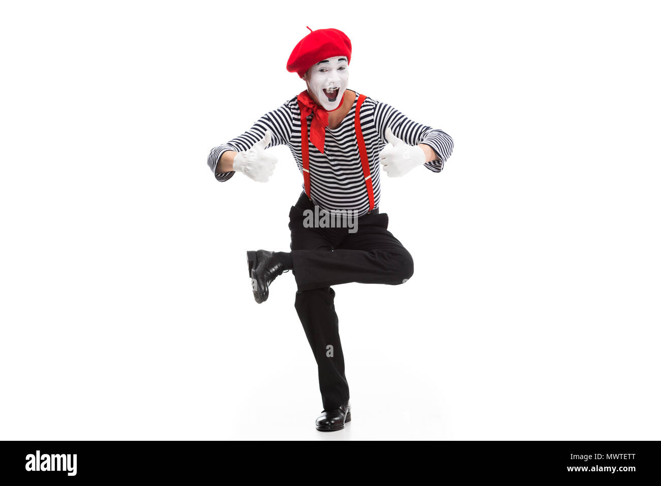 funny mime performing on one leg and showing thumbs up isolated on white - Stock Image