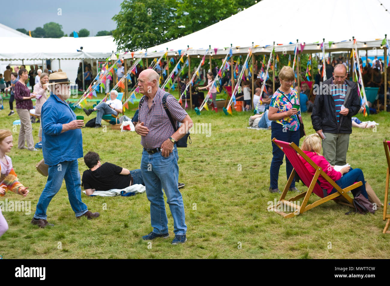 Visitors relaxing on the lawn in the garden area at Hay Festival 2018 Hay-on-Wye Powys Wales UK - Stock Image
