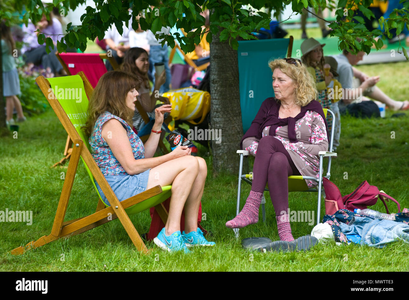Ladies sat in deckchairs chatting on the lawn in the garden area at Hay Festival 2018 Hay-on-Wye Powys Wales UK - Stock Image