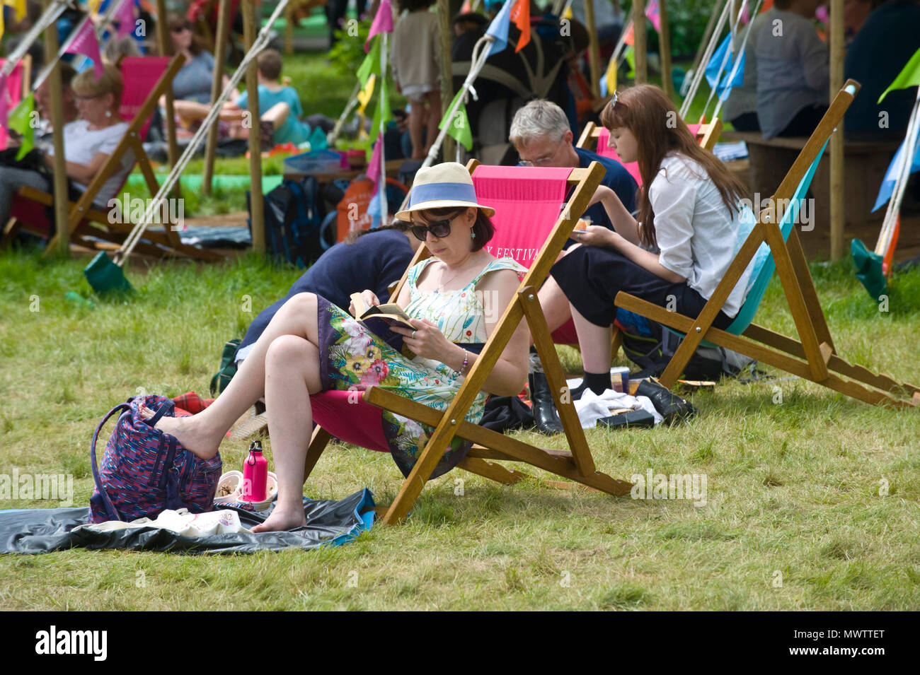Young woman sat in deckchair reading a book on the lawn in the garden area at Hay Festival 2018 Hay-on-Wye Powys Wales UK - Stock Image