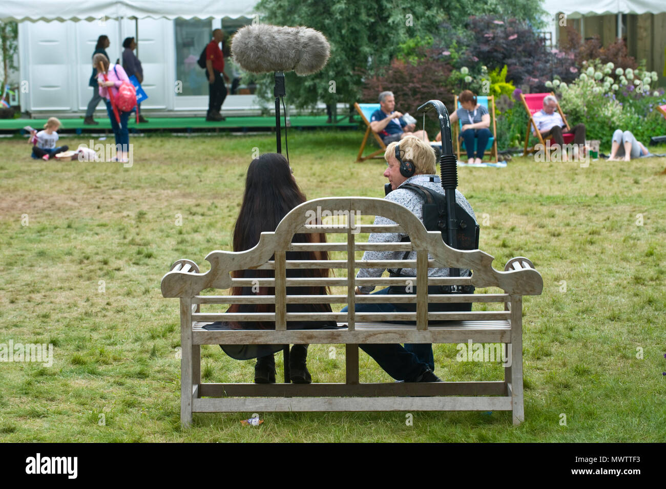 TV crew sat on bench chatting in the garden area at Hay Festival 2018 Hay-on-Wye Powys Wales UK - Stock Image