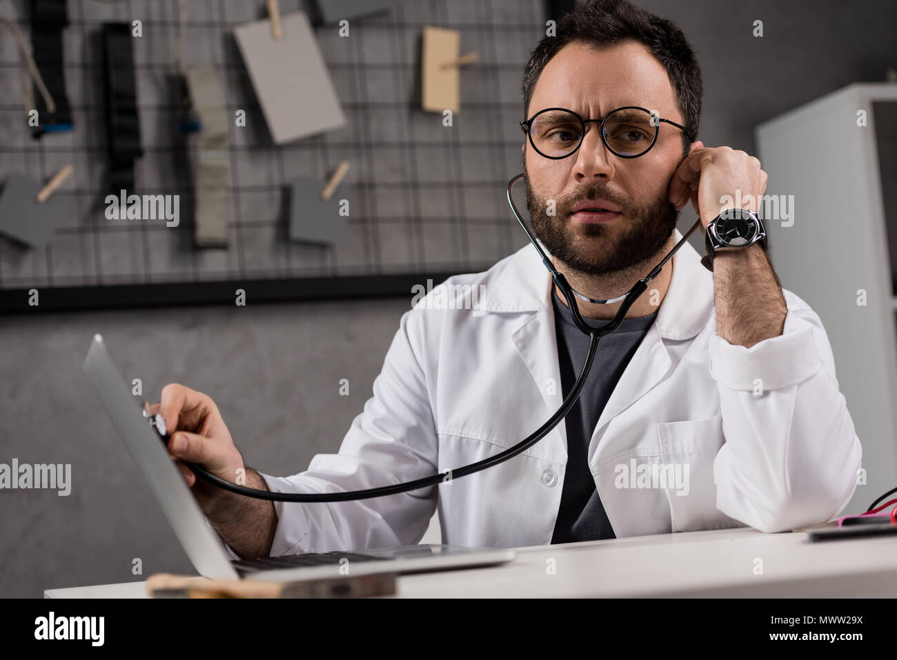 man in white coat and stethoscope diagnosing laptop - Stock Image